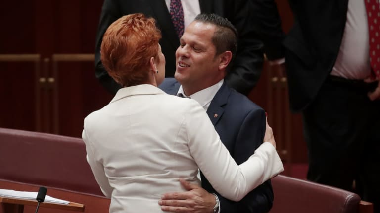 Senator Pauline Hanson embraces Senator Peter Georgiou after he delivered his first speech to the Senate on Wednesday.