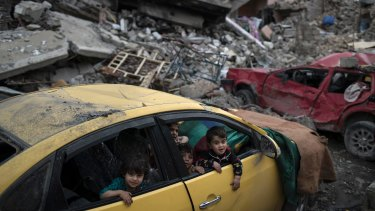 Children play inside a damaged car in a neighbourhood recently retaken by Iraqi forces.