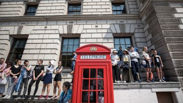 Tourists stand on a wall near a traditional red telephone box to try and catch a glimpse of Queen Elizabeth II on Wednesday.