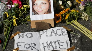 A makeshift memorial of flowers and a photo of victim Heather Heyer sits in Charlottesville, Virgnia on Sunday.