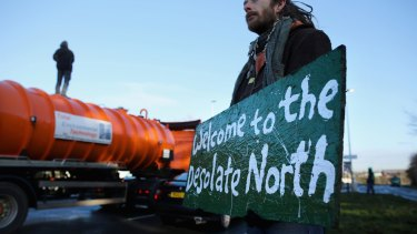 An anti-fracking protester stands on top of a truck carrying chemicals to the Barton Moss gas fracking facility in 2014.