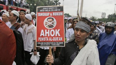 "A man holds a poster during a rally against Jakarta's then governor Basuki ""Ahok"" Tjahaja Purnama, a Christian accused of blaspheming against Islam."