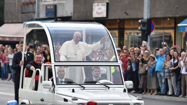 Pope Francis waves to the crowd from the popemobile on Saturday.