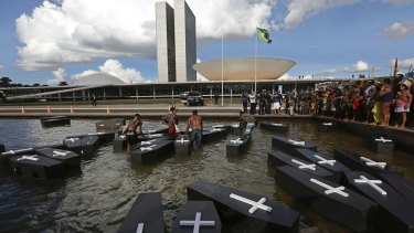 Indigenous protesters from various ethnic groups place fake coffins, representing indians killed over the demarcation of land, in a water feature outside Brazil's National Congress.