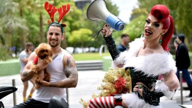 Tom Gough, left, with Poppy Maus the toy poodle, and drag queen Art Simone at the Chapel Street Christmas parade.