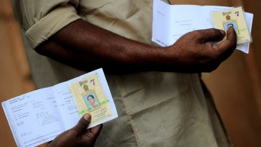 People have their identity and polling cards ready as they queue to vote.