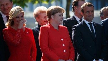 German Chancellor Angela Merkel, French President Emmanuel Macron and other leaders smile as President Trump speaks.