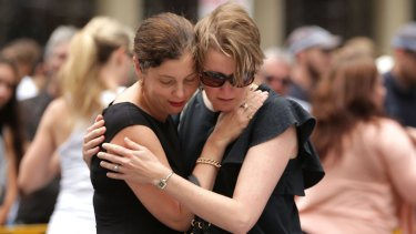 Women comfort each other in Martin Place this week.