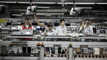 Workers assemble monitors at a TCL factory in Guangdong province, China.