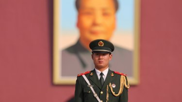 A guard stands in front of the portrait of Chairman Mao at Tian'anmen Square