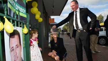 Marty Corboy's daughter Bridget Corboy, 4, watches National Party leader Barnaby Joyce put his country hat on Fiona Nash.