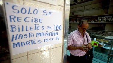 A man counts his 100-bolivar notes next to a sign on a bakery wall alerting customers that 100-bolivar notes will only be accepted until Tuesday,  December 13.