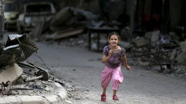 A girl runs near damaged buildings and debris in Jobar on Wednesday.