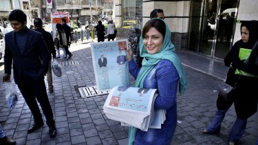 An Iranian election campaign worker distributes electoral leaflets of reformist candidates in downtown Tehran.