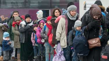 Refugees walk to a chartered train at the railway station of Passau, Germany on Tuesday.