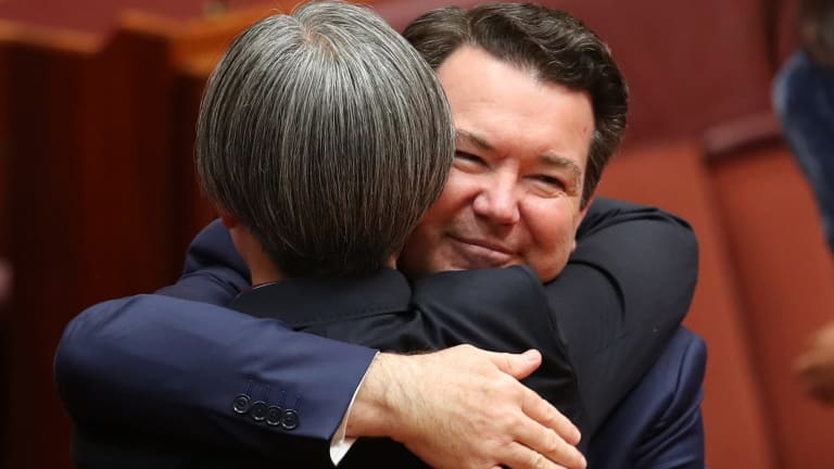 Senator Penny Wong is hugged by co-sponsor Senator Dean Smith after speaking on the Marriage Amendment Bill at Parliament House in Canberra.