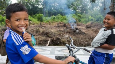 Children ride their bicycles in Pelalawan, in Riau province as small fires burn in the background.