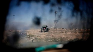 Iraqi police forces fire from a humvee at Islamic State positions from a hillside near Mosul on Monday.