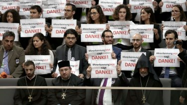 """Guests hold posters reading """"Recognition Now says thank you"""" during a meeting of the German federal parliament."""