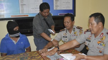 From left, seated: Captain Yohanis Humiang with head of the people smuggling division of Nusa Tenggara Timur, Ibrahim, and Rote police chief Hidayat.