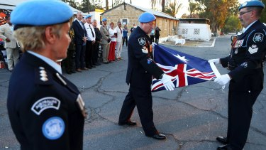 Australian UN police officers fold the Australian flag during a flag-lowering ceremony to end Australia's peacekeeping contribution in Cyprus on Friday.