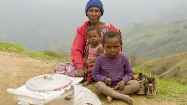 Gima Hebe and her two grandchildren trying to sell fried flour balls on the ridge above Odinoma village on Gun-Beroma Road.