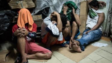 Alleged drug suspects cover their faces during a drug raid on December 9, 2016 in Manila, Philippines.