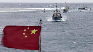 Chinese fishing boats sail in the lagoon of Meiji reef in the South China Sea, an islet also claimed by Vietnam.