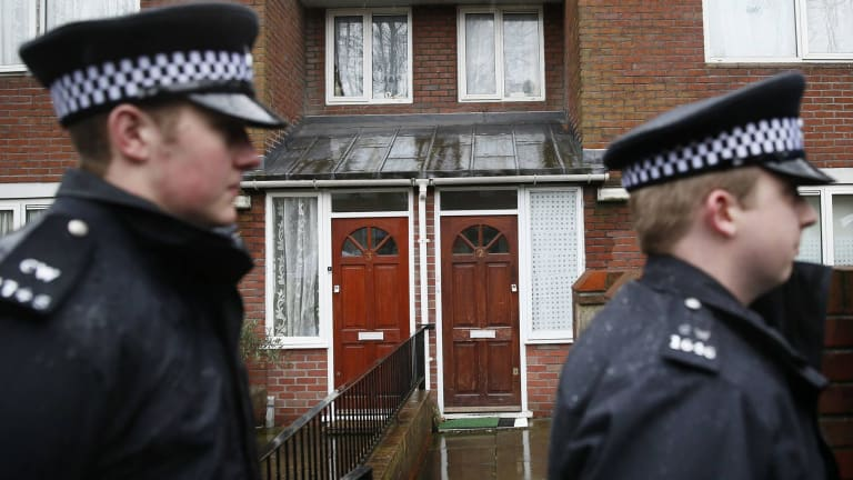 Two police officers walk outside a flat in London that was the former home of  Mohammed Emwazi.