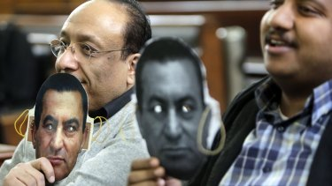 Supporters of Egypt's ousted President Hosni Mubarak hold masks with Mubarak's face during a session at the Cairo High Court in Egypt on Thursday. Mubarak is being retried over the killing of hundreds of protesters during the 2011 uprising that ended his nearly three decades in power.