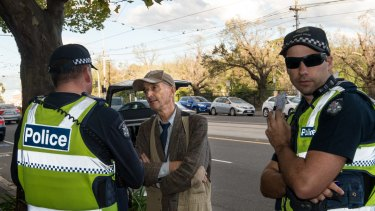 Police question a man outside the East Melbourne fertility clinic on Monday.