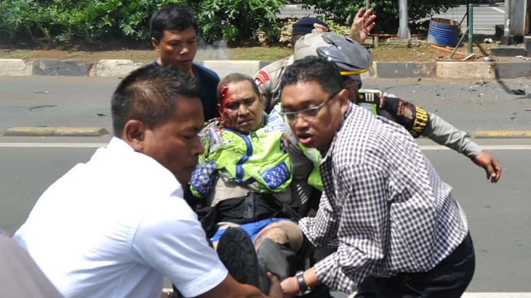 People carry an injured police officer near the site where an explosion went off at a police post in Jakarta.