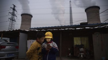 Boys look at a phone next to a coal-fired power plant on the outskirts of Beijing in November.