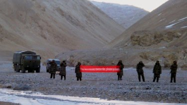 "Chinese troops hold a banner reading ""You've crossed the border, please go back"" in Ladakh, India."