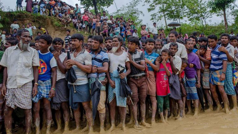Rohingya Muslim men, who crossed over from Myanmar into Bangladesh, wait for their turn to collect food at a refugee camp.