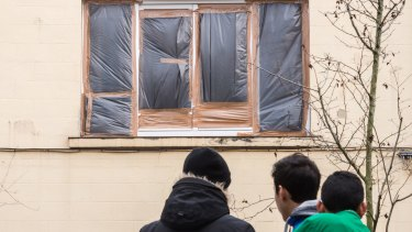 The broken windows of a house in which terror suspects were hiding are covered with plastic the day after the raid.
