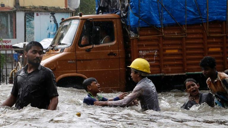 Children play in a waterlogged street during heavy rains in Mumbai.