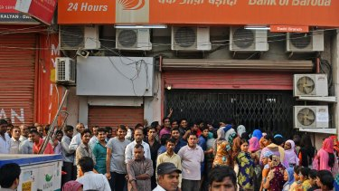 Rupee withdrawal: customers wait in line to exchange discontinued rupee banknotes at a Bank of Baroda branch in Dadri, Uttar Pradesh, India.