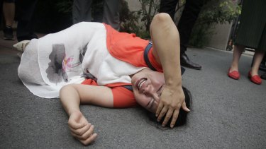 Fan Lili, the wife of imprisoned activist Gou Hongguo, lies on the ground after being knocked over by plainclothes officers outside the Tianjin No. 2 Intermediate People's Court on Monday.