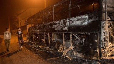 Residents walk past a burnt bus as a wildfire moves forward in Chandebrito in the north-western Spanish region of Galicia.