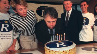 Malcolm Turnbull blows out the candles on a cake marking seven years of the ARM, flanked by Wendy Machin and Neville Wran.