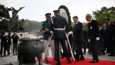 South Korea's new President Moon Jae-In, centre right, offers a wreath at the National Cemetery.