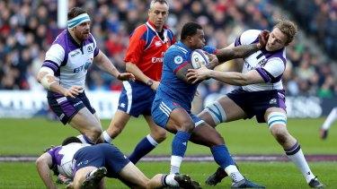 France's Virimi Vakatawa, center, is tackled by Scotland's Jonny Gray.