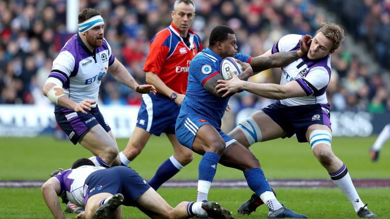 France's Virimi Vakatawa, center, is tackled by Scotland's Jonny Gray.