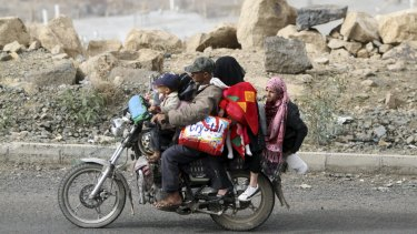 A man flees with his family and their belongings on a motorcycle in Sanaa, Yemen.