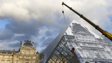 A technician pastes a giant picture on the Louvre Pyramid as part of JR's eye-tricking installation on Monday