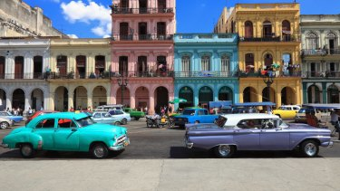 Vintage American cars, imported prior to the trade embargo, moving on the streets of colourful Havana, Cuba.