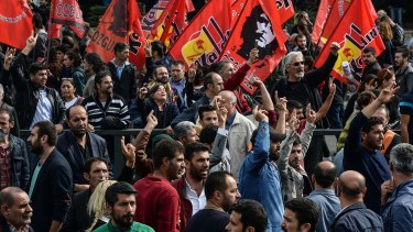Protesters carry flags and pictures of the victims of Saturday's bomb blasts in Ankara on Sunday.