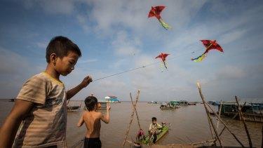 Children fly kites in the floating village.