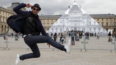 JR poses in front the Louvre Pyramid in Paris on Tuesday.